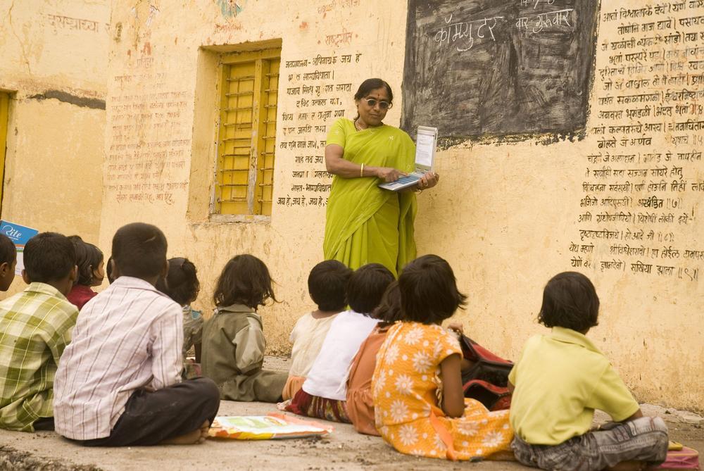 Grundschullehrerin in Indien mit einem Laptop, im Hintergrund ein Text in Hindi an der Wand.