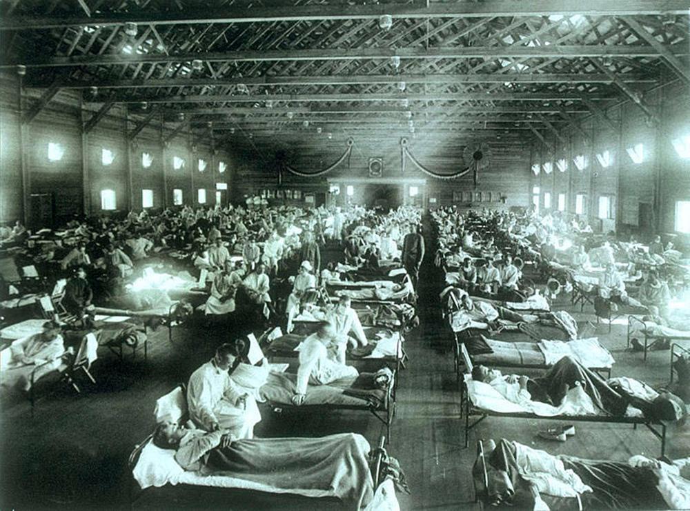 Blick in eine lange Halle mit Betten in Reih und Glied. Darin liegen Patienten. Bild in Schwarzweiß.