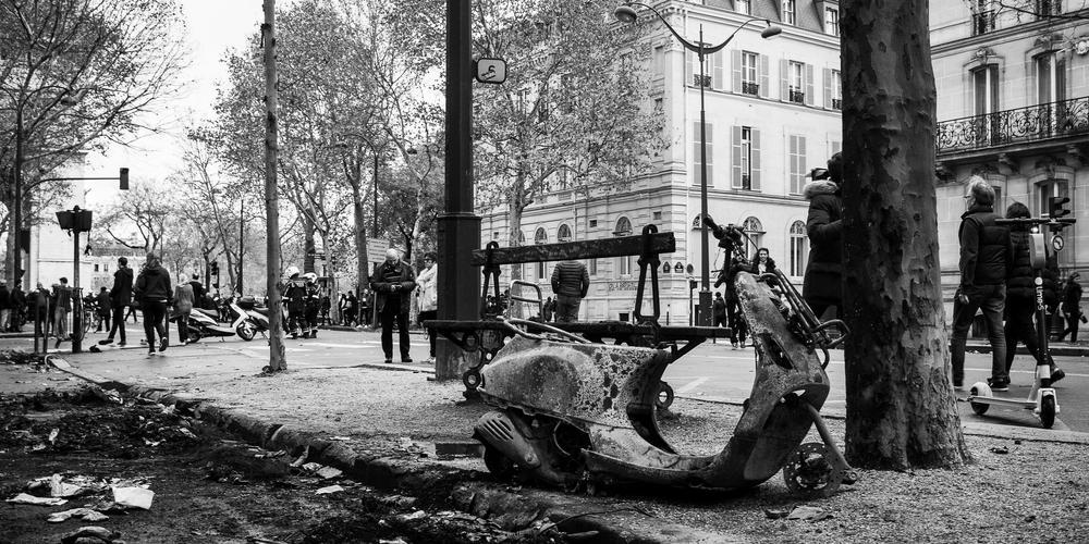 Ein abgebranntes Motorad steht am Straßenrand. Demonstranten gehen auf der Straße vorbei. Aufnahme in Schwarz-Weiß.