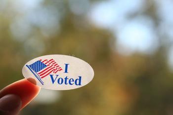 """Aufkleber mit der Aufschrift """"I voted"""" auf einer Fingerspitze."""