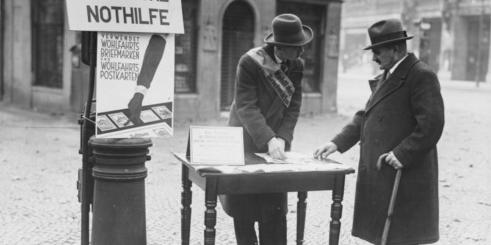 Schwarzweiß-Aufnahme vom Vorkauf von Wohlfahrtsmarken 1929. Ein Mann hinter einem Tisch stehend händigt eine Marke einem Mann davor aus.