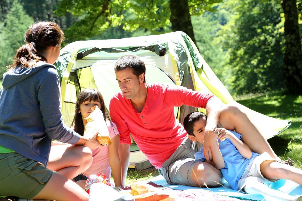 Familie bei Sonnenschein vor einem Zelt auf Isomatten liegend.