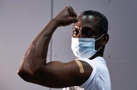 Ein schwarzer Mann, der ein weißes T-Shirt trägt, hält seinen linken Arm hoch, auf dem recht weit oben ein Pflaster klebt.