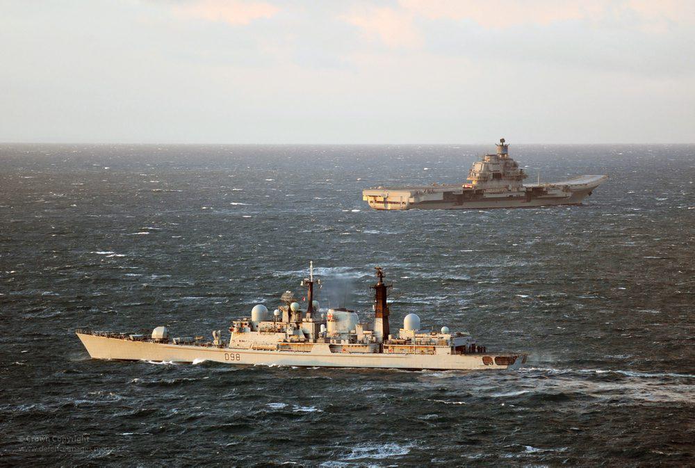 Ein russischer Flugzeugträger wird von einem britischem Zerstörer auf hoher See aus nicht allzu großer Entfernung begleitet.