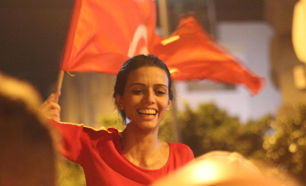 Eine junge Frau schwenkt bei einer Demonstration eine rote tunesische Flagge. Sie ist im Mittelpunkt, die Gestalten um sie herum sind nur unscharf zu erkennen.