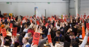 Abstimmung in einer Halle mit Nein-Karten.