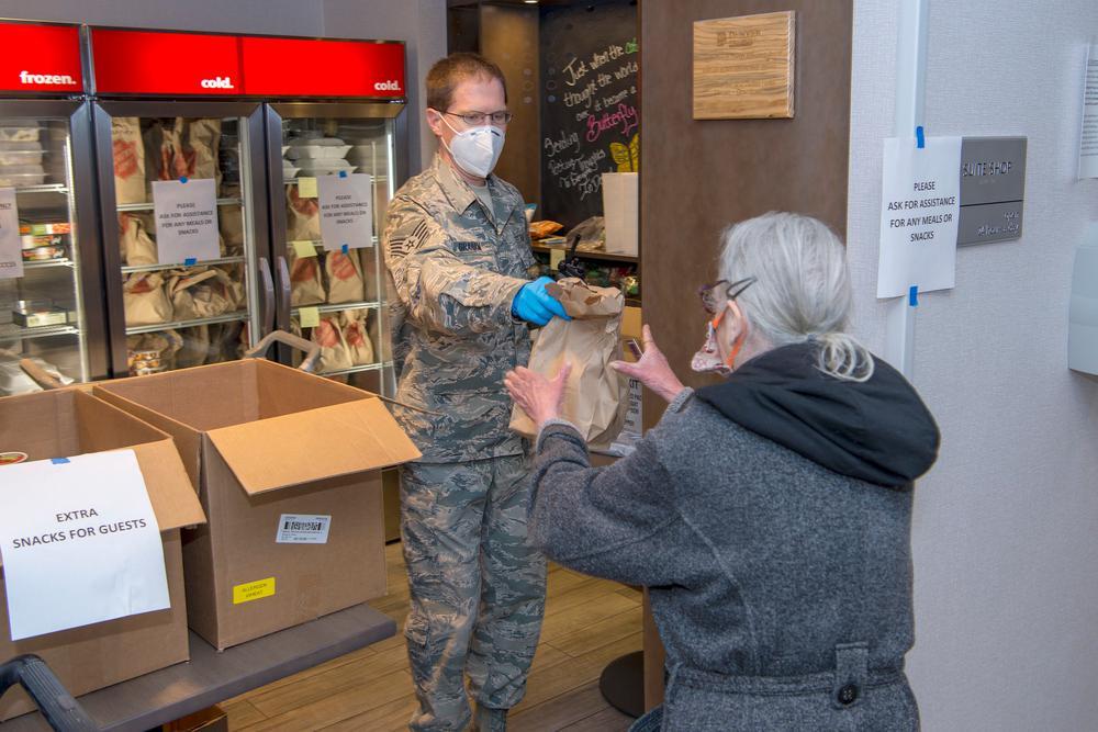 Ein Mann in Tarnkleidung reicht einer Frau eine Tüte bei einer Essensausgabe für arme Menschen.