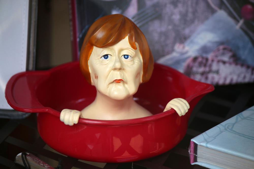 Plastikobjekt, das Angela Merkels Kopf zeigt, der aus einer roten Wanne schaut.