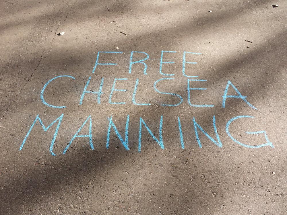 Kreideschrift auf Asphalt: Free Chelsea Manning.