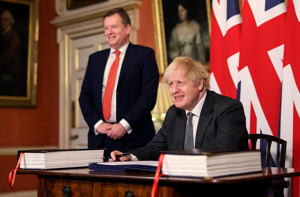 Boris Johnson unterzeichnet ein Dokument an einem Tisch, hinter ihm mehrere Flaggen des Vereinigten Königreiches.