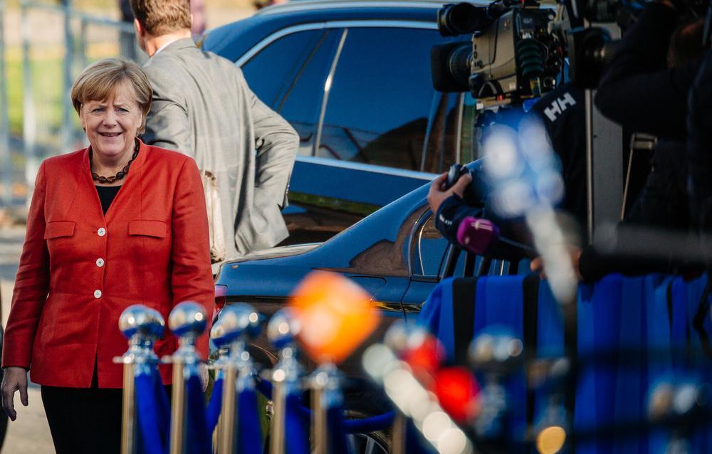 Angela Merkel steht am linken Bildrand und blickt auf wartende Kameras, die rechts etwas weiter vorn im Bild stehen.