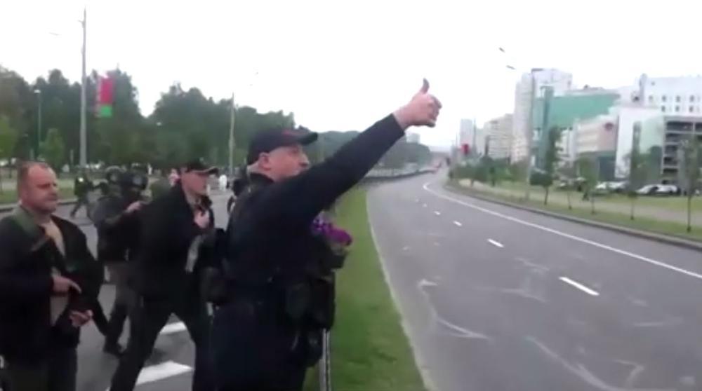 Aljaksandr Lukaschenka steht mitten auf einer leeren Straße, hinter ihm Sicherheitsleute in schwarzer Kleidung.