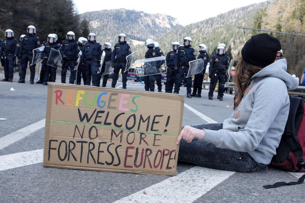 Polizei sperrt eine Straße, auf der eine Demonstrantin mit einem Schild sitzt.