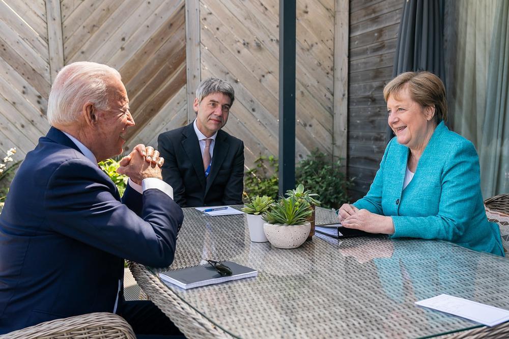 Joe Biden und Angela Merkel sitzen sich an einem Holztisch gegenüber, am Kopfende sitzt ein Übersetzer.