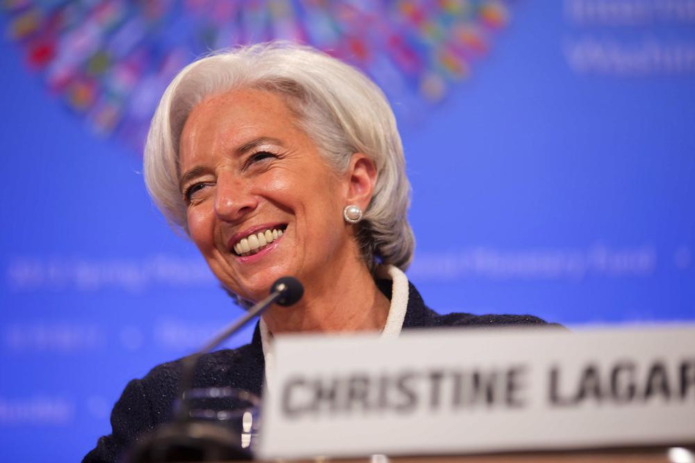 Christine Lagarde lächelnd hinter einem Tisch mit Mikro.