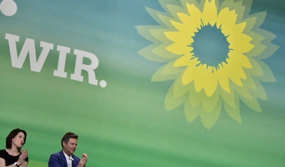 Vor einer großen grünen Wandfläche mit einer angedeuteten Sonnenblume oben rechts stehen links unten, nur klein zu sehen, Annalena Baerbock und Robert Habeck.