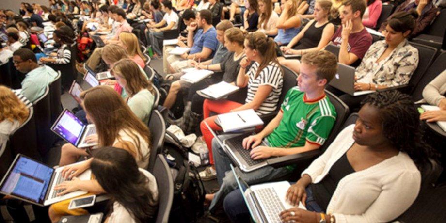 Studenten sitzen in einem Vorlesungssaal, von der Seite aufgenomen. Einige haben Labtops auf den Knien, andere Notizhefte.