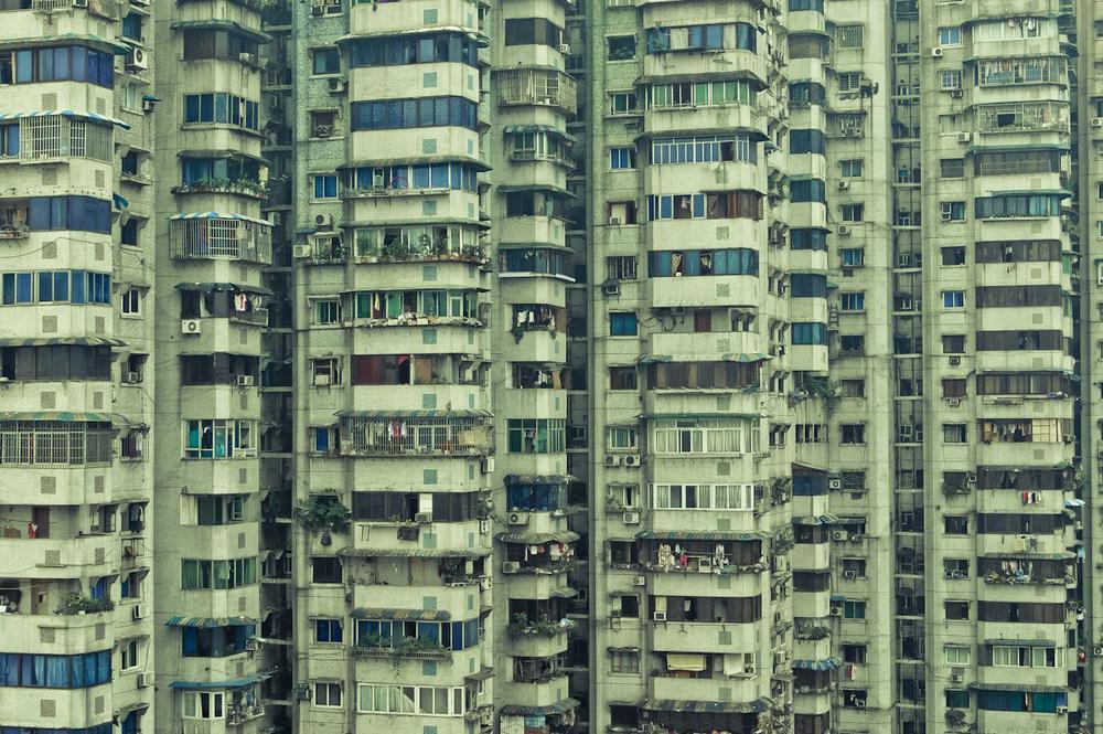 Front eines hohen grün-grauen Mietshauses in Peking.
