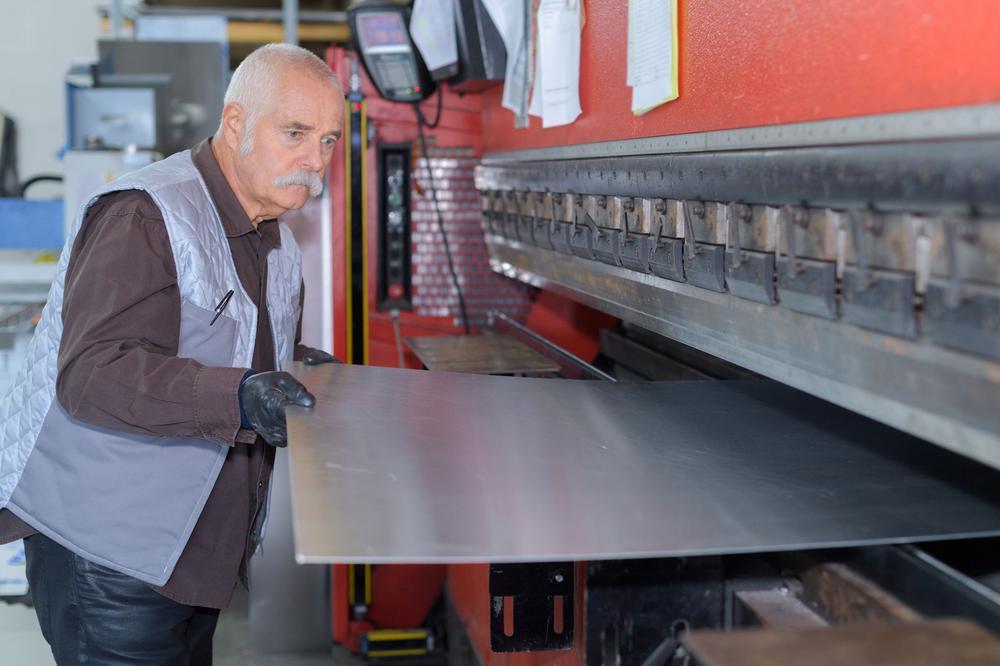 Älterer Arbeiter schiebt eine Stahlplatte in eine Presse.