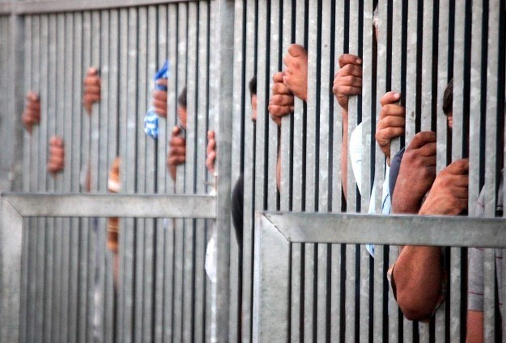Eine Flucht von vergitterten Gefängniszellen, die nach hinten unscharf wird. Zwischen den Gittern sind Hände zu sehen, die die Gitterstäbe umfassen.