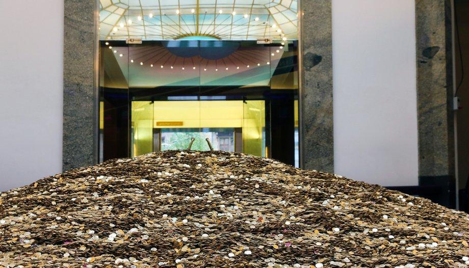 Ein Haufen Münzen ist im Eingang eines schicken Gebäudes aufgehäuft.