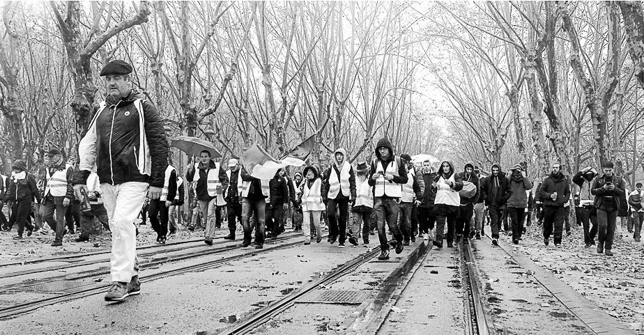 Protestzug der Gelbwesten bei Regenwetter auf nasser Straße. Aufnahme in Schwarzweiß.