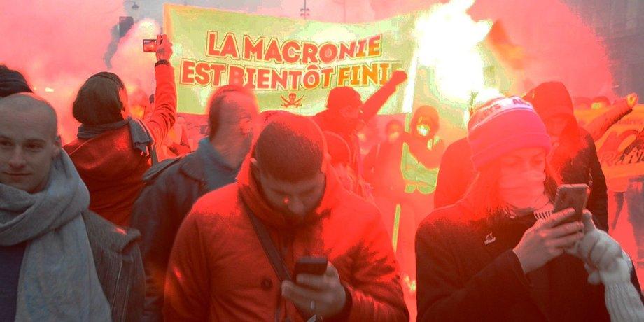 Demonstrationszug in Paris mit großem Transparent gegen Macron und rotleuchtenden Fackeln. Im Vordergrund blicken Demonstranten auf ihre Handys.