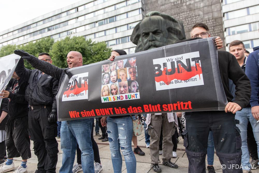 Männer stehen vor einem Karl-Marx-Denkmal und halten ein Transparent, auf dem steht: Wir sind bunt, bis das Blut spritzt.