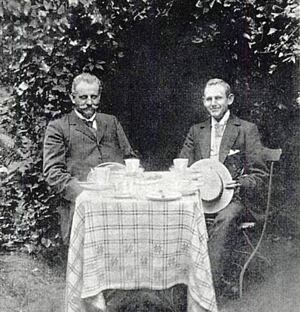 Ein älterer und ein jüngerer Mann sitzen an einem Gartentischchen vor einem großen Busch. Das Bild ist schwarzweiß und schon leicht verblichen.