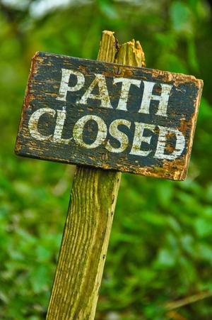 "Holzschild im Grünen mit der Aufschrift: ""Path closed"" (Weg gesperrt)."