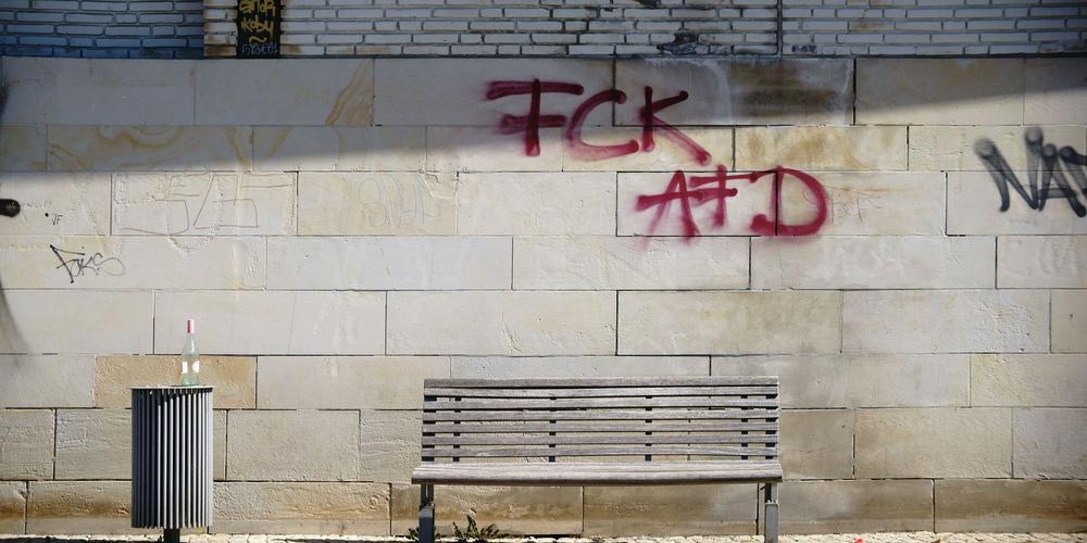 """Wand mit dem Graffity """"FCK AFD"""" hinter einer Parkbank."""