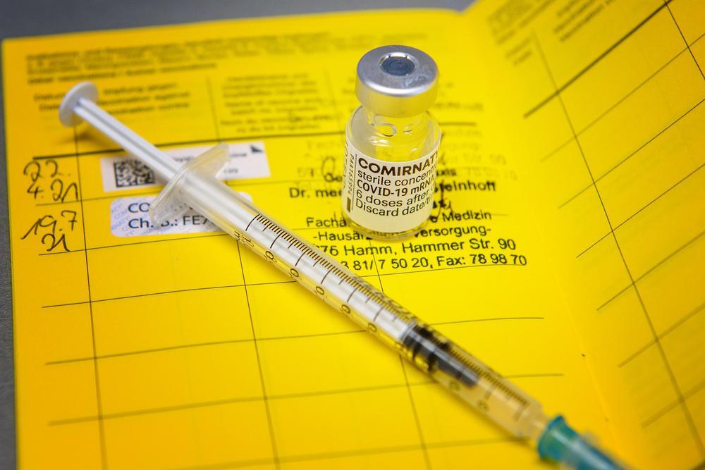 Eine Spritze liegt neben ein kleinen Glasampulle mit Corona-Impfstoff auf einem gelben Impfausweis.
