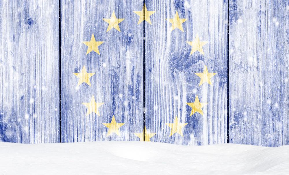 EU-Sterne auf einer blauen Bretterwand mit Schnee davor.