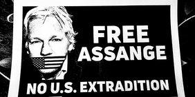 """Plakat mit der Aufschrift """"Free Assange"""" und einem Foto Julian Assanges, denn Mund mit einer US-Flagge verbunden ist."""