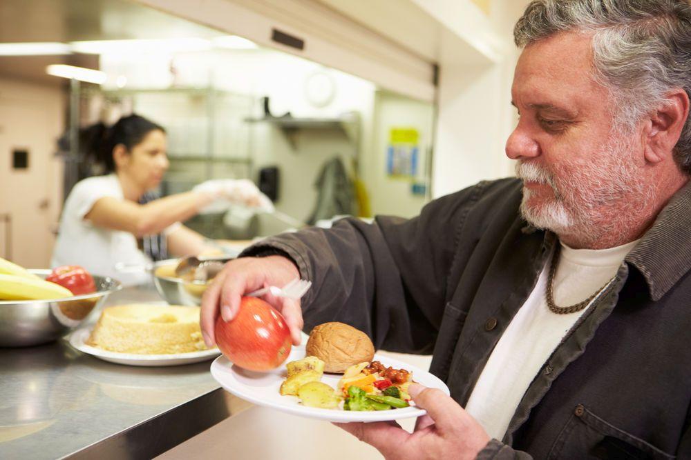 Ein bärtiger Mann nimmt an einer Theke ein Tablett mit Essen entgegen, auf das er noch einen Apfel legt.