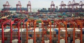 Container so weit das Auge reicht in einem Hafen mit Kränen.