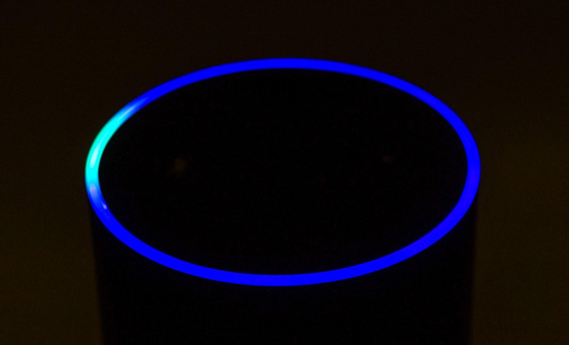 Echo-Box von Amazon, die auch ein Mikro enthält, im Dunkeln, nur durch einen blauleuchtenden Ring zu erkennen.