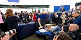 Jean-Claude Juncker sitzt an einem Tisch umringt von Journalisten.