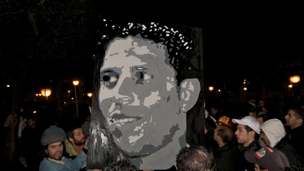 Männer tragen ein großes Gemälde eines Mannes bei einer Demonstration.