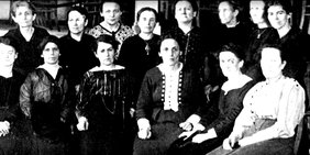 Historisches Schwarzweißbild von Frauen, vorne sitzend, dahinter stehend, die streng in die Kamera blicken