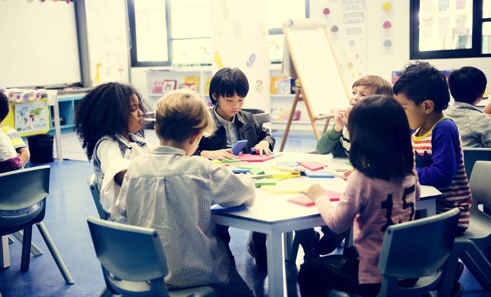 Kleine Kinder unterschiedlicher Herkunft sitzen in einer Schule rund um einen Tisch und lernen.