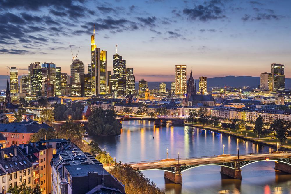 Nächtliche Skyline von Frankfurt mit beleuchteten Hochhäusern.