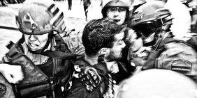 Ein Protestierender ist von drei Polizisten mit Helmen eingekeilt und wird mitgenommen.