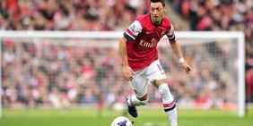 Mesut Özil mit dem Ball am Fuß im Trikot von Arsenal London stürmt auf grünem Rasen voran.