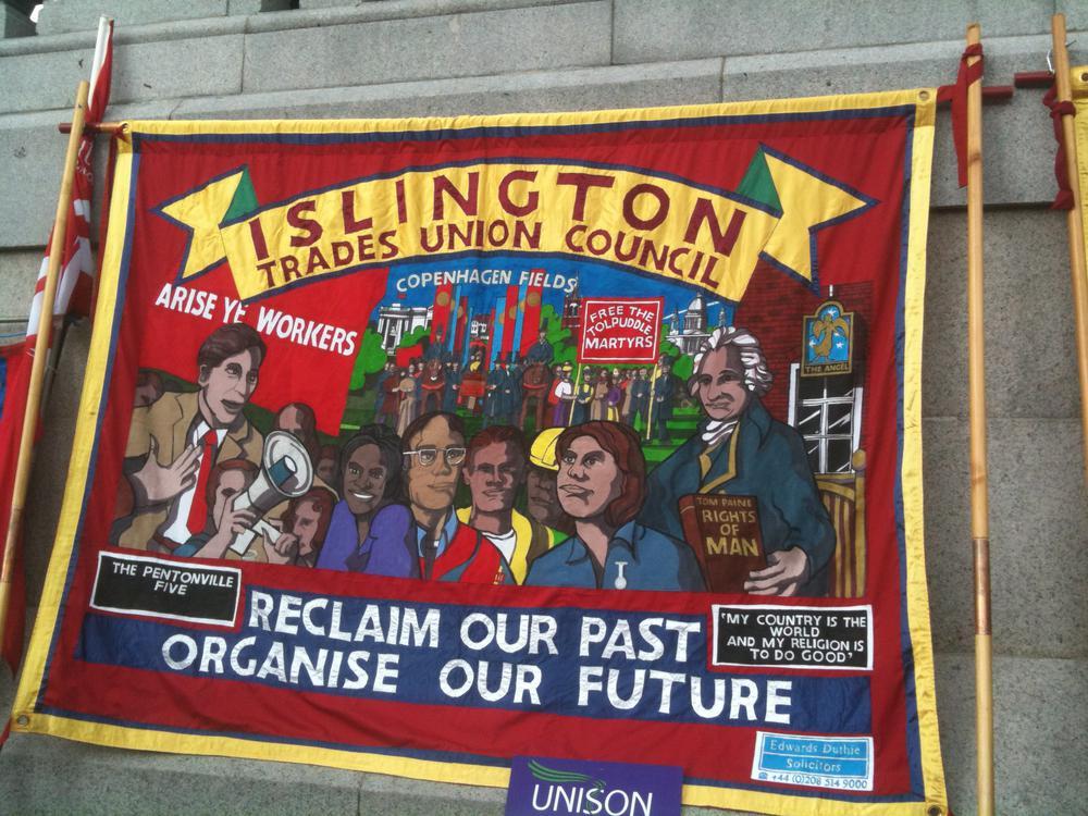 Rotes Transparent der Gewerkschaftfen mit Forderungen für bessere Arbeit.