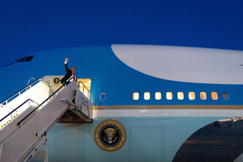 Donald Trump steht am oberen Ende der Gangway kurz vor dem Einstieg in Air Force One und winkt in den dunkelblauen Abendhimmel.