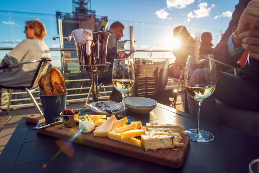 Ein Dachrestaurant bei strahlendem Sonnenschein, mit Weingläsern und einer Käseplatte auf einem Tisch im Vordergrund und Gästen in Sesseln im Hintergrund.