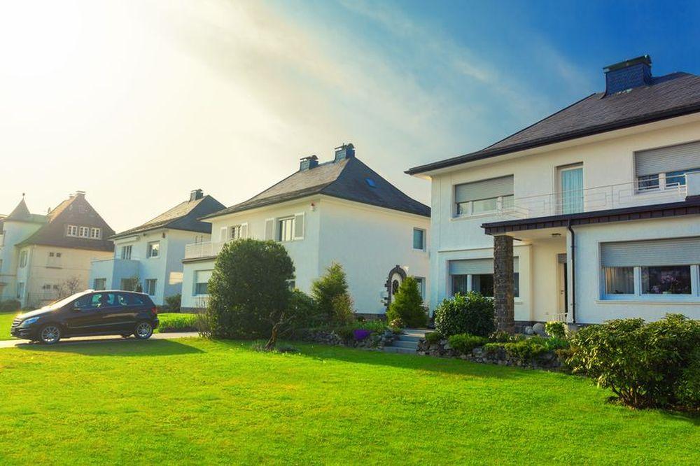 Einfamilienhäuser in einer Vorstadt mit Garten und Auffahrt, auf der ein Auto steht.