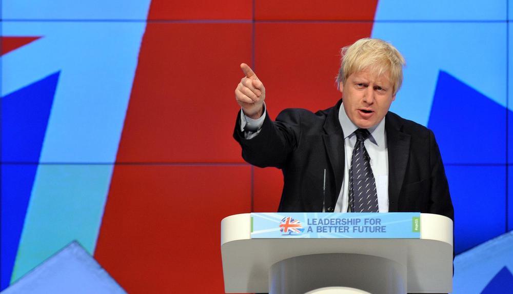 Boris Johnson bei einer Rede vor blauem Hintergrund.