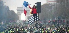 Eine Frau steht auf einer Ampel und schwenkt die französische Fahne bei einer Demonstration vor dem Arc de Triomphe in Paris.
